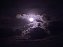 Full moon behind stormy clouds