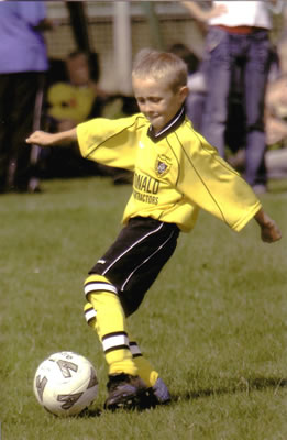 Young boy in yellow team shirt playing football (soccer)