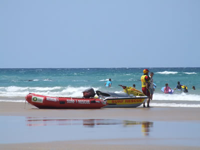 Surf rescue rubber boat and jet ski on beach with lifeguard