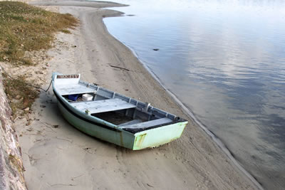 old small row boat on beach. Dinghy